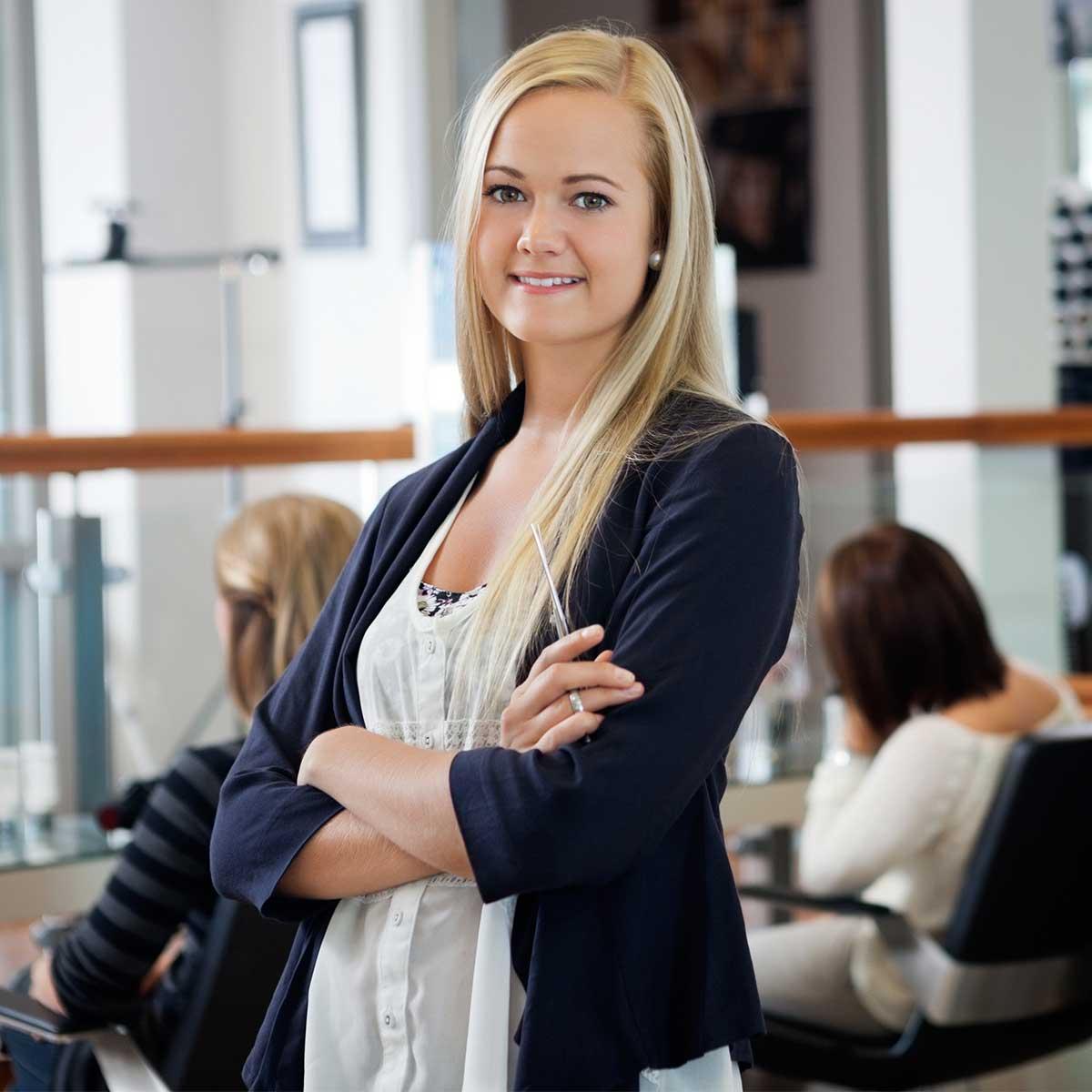 Vaaleatukkainen kampaamoyrittäjä odottaa asiakasta